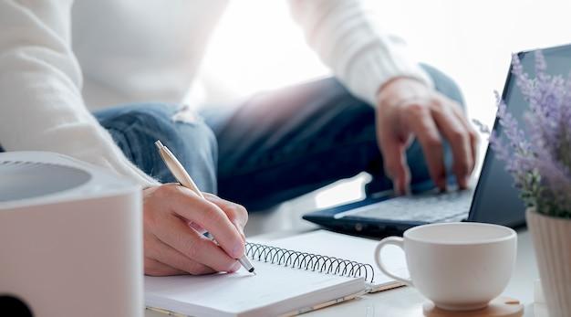 Vista lateral da mão do homem escrevendo no caderno com caneta enquanto trabalhava em casa.