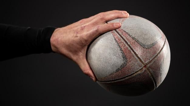 Vista lateral da mão do jogador de rugby segurando uma bola
