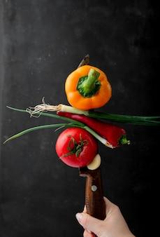 Vista lateral da mão feminina com uma faca com legumes frescos maduros pimentão amarelo cebola verde pimenta vermelha e tomate em fundo preto