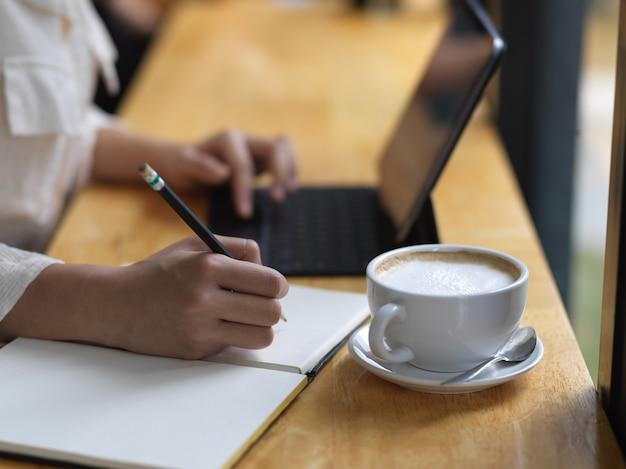Vista lateral da mão feminina escrevendo no caderno em branco enquanto trabalhava com o tablet na barra de madeira