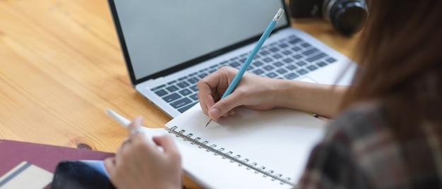 Vista lateral da mão feminina, escrevendo no caderno em branco enquanto usa o tablet simulado na mesa de madeira