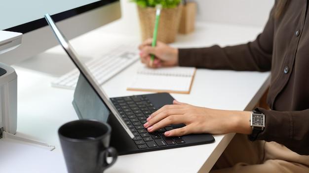 Vista lateral da mão feminina trabalhando com tablet digital e escrevendo no caderno na mesa do computador
