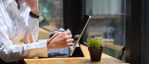 Vista lateral da mão feminina usando tablet digital com caneta stylus na mesa de madeira