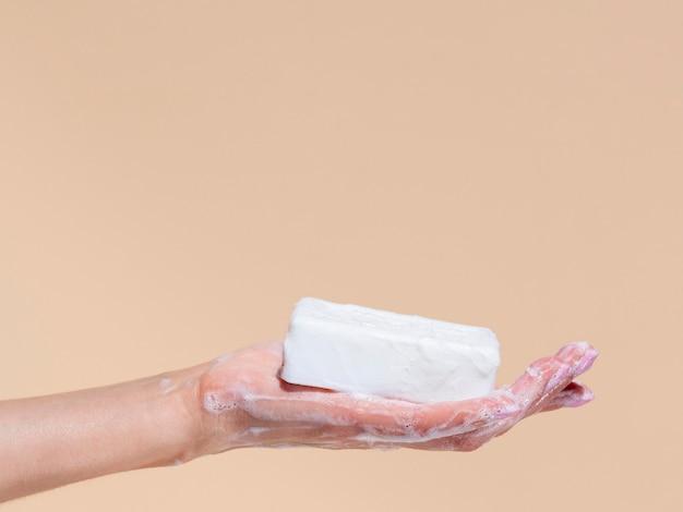 Vista lateral da mão segurando a barra de sabão com espaço de cópia
