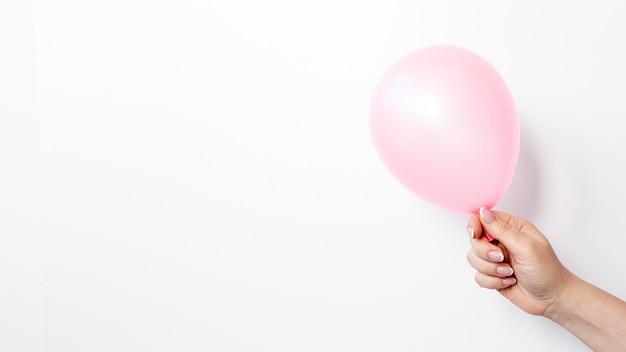 Vista lateral da mão segurando balão para dia dos namorados