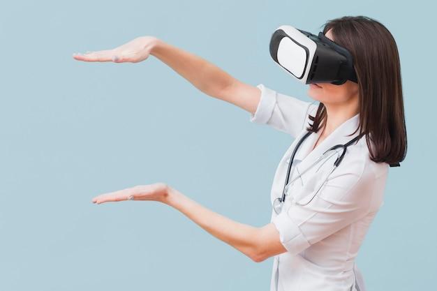 Vista lateral da médica com fone de ouvido de realidade virtual