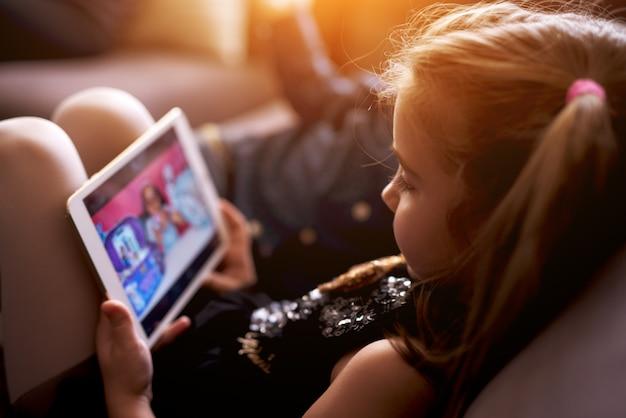 Vista lateral da menina assistindo desenho animado sentado no sofá