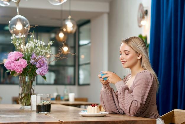 Vista lateral da menina bonita tomando café no café local com interior elegante.