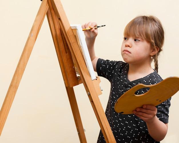 Vista lateral da menina com síndrome de down pintura com cavalete