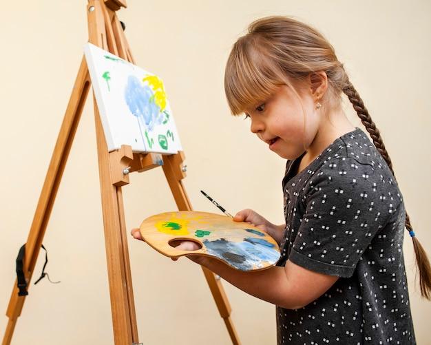 Vista lateral da menina com síndrome de down, segurando a paleta