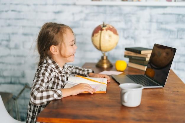 Vista lateral da menina da escola criança positiva alegre aluno fazendo lição de casa tendo aula online e olhando para a tela do computador portátil com um sorriso encantador. conceito de educação de e-learning online.