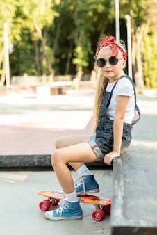 Vista lateral da menina de macacão azul