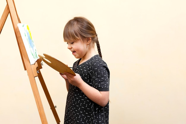 Vista lateral da menina feliz com síndrome de down pintura
