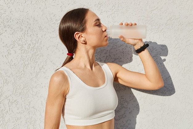 Vista lateral da menina morena com rabo de cavalo usando blusa branca, bebendo água da garrafa durante o treino ao ar livre, sentindo sede ao fazer exercícios de esporte.