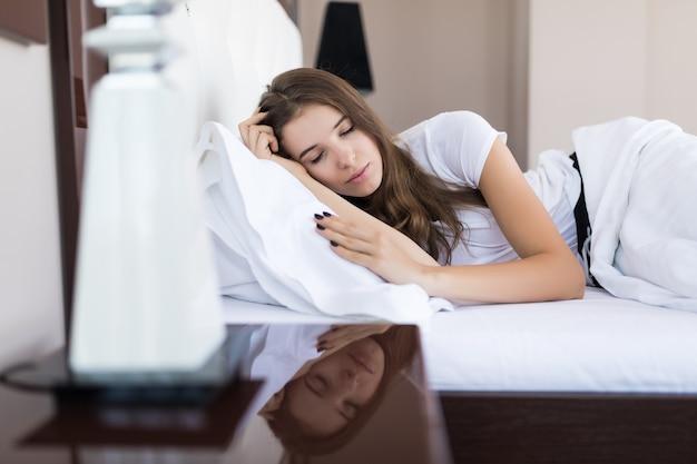 Vista lateral da menina morena feliz dormindo acordando de manhã na cama