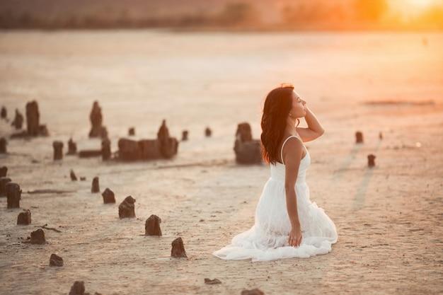 Vista lateral da menina morena que está sentado sobre os joelhos na areia por do sol