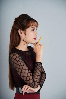 Vista lateral da menina, ponderando sobre a tarefa de negócios com uma caneta na mão