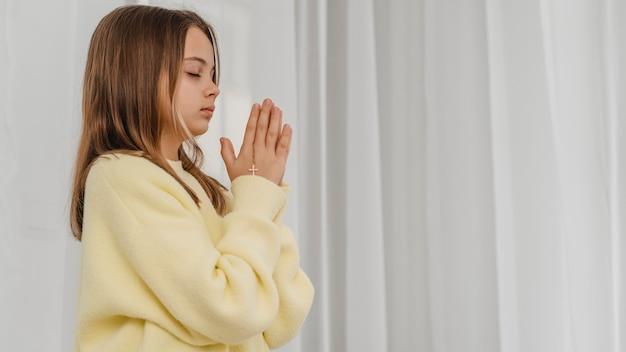 Vista lateral da menina rezando com espaço de cópia
