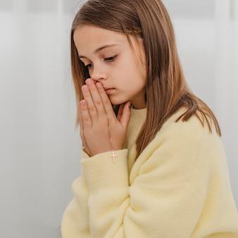 Vista lateral da menina rezando em casa