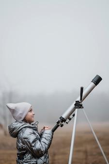 Vista lateral da menina usando um telescópio