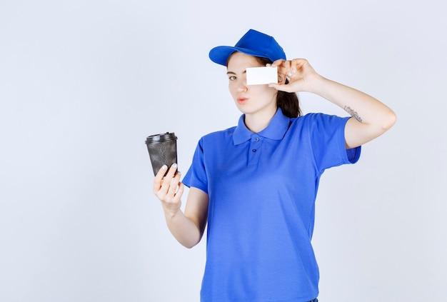 Vista lateral da mensageira que esconde o olho esquerdo com o cartão enquanto segura o café na mão