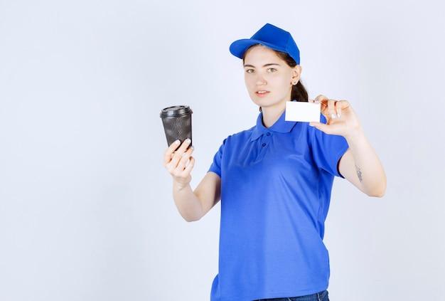 Vista lateral da mensageira que mostra o cartão enquanto segura o café com a mão direita em frente à parede branca