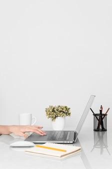 Vista lateral da mesa com as mãos e laptop