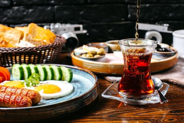 Vista lateral da mesa de café da manhã com ovo frito e salsichas legumes frescos queijo e presunto