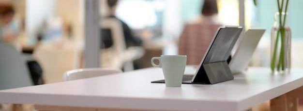 Vista lateral da mesa de escritório confortável com laptop, tablet, caneca e decoração