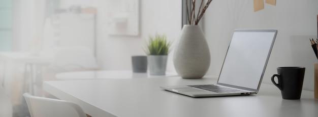 Vista lateral da mesa de escritório em casa mínima com laptop de tela em branco, decorações e espaço de cópia