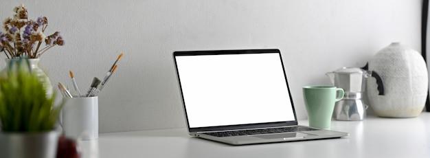 Vista lateral da mesa de escritório moderna com laptop de tela em branco, ferramentas de pintura e decorações