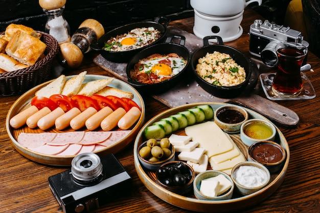 Vista lateral da mesa do café da manhã com salsichas legumes frescos queijo presunto e molhos jpg