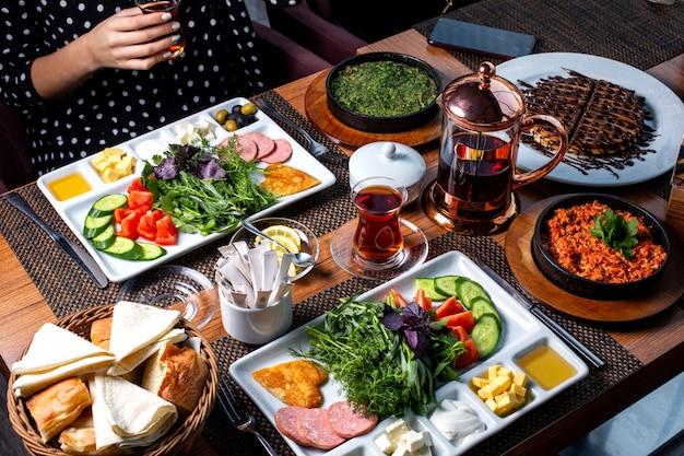 Vista lateral da mesa do café da manhã servida com vários alimentos ovos fritos salsichas queijo salada fresca sobremesa e chá