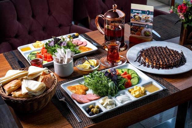 Vista lateral da mesa do café servida com vários alimentos sobremesa e chá