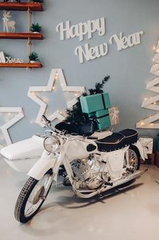 Vista lateral da motocicleta retro branca carregada com presentes de natal verdes embrulhados do papai noel e a árvore de natal do abeto. moto com presentes na sala decorada.
