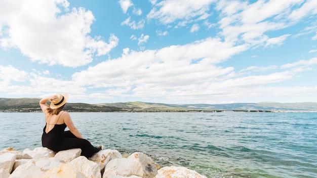 Vista lateral da mulher admirando o oceano em um lindo dia