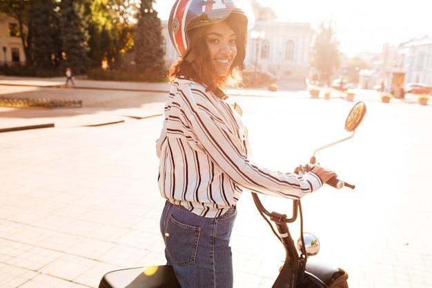 Vista lateral da mulher africana despreocupada monta na moto moderna ao ar livre e olhando para a câmera