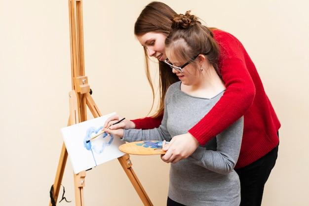 Vista lateral da mulher, ajudando a garota com síndrome de down pintura