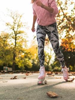 Vista lateral da mulher andar de patins em caneleiras
