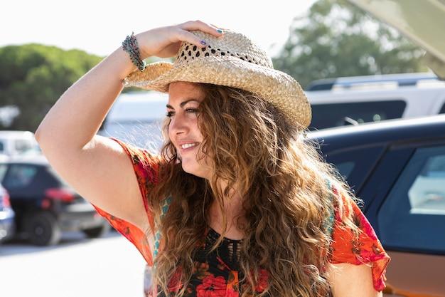 Vista lateral da mulher ao ar livre com chapéu