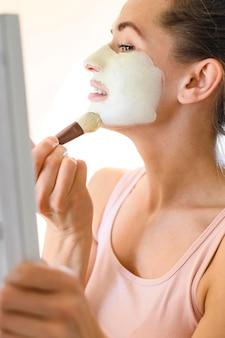 Vista lateral da mulher aplicar máscara facial