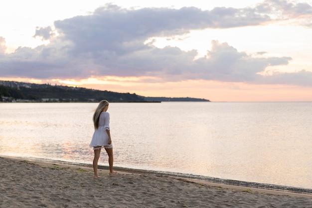 Vista lateral da mulher, apreciando a vista da praia
