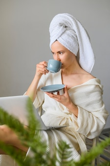Vista lateral da mulher, aproveitando o dia do spa em casa enquanto tomando café