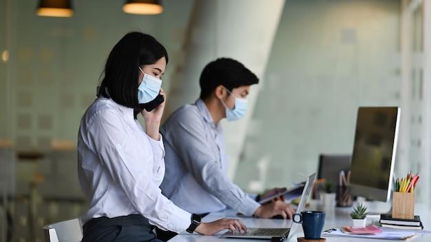 Vista lateral da mulher asiática do empregado do escritório usando máscara protetora de trabalho no novo escritório normal com seu colega.