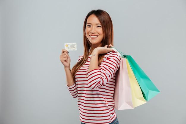 Vista lateral da mulher asiática feliz na camisola segurando o cartão de crédito e compra enquanto olha para a câmera sobre fundo cinza