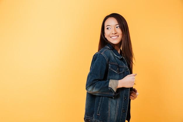 Vista lateral da mulher asiática feliz na jaqueta jeans posando e olhando para trás sobre fundo amarelo