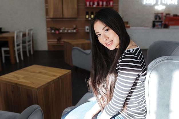 Vista lateral da mulher asiática, sentado na cantina