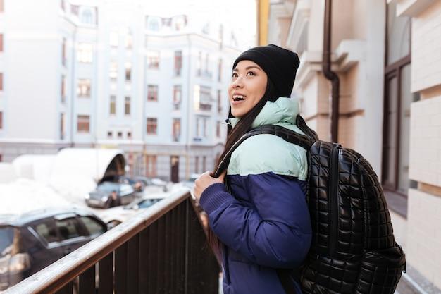 Vista lateral da mulher asiática sorridente em roupas quentes