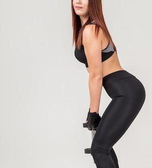 Vista lateral da mulher atlética fazendo agachamentos, mantendo o peso