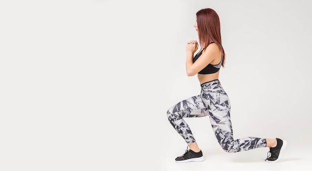 Vista lateral da mulher atlética fazendo lunges